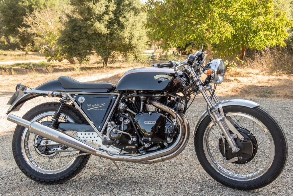 The side view of a black-and-silver 1968 Egli-Vincent by Godet on a sunlit gravel driveway