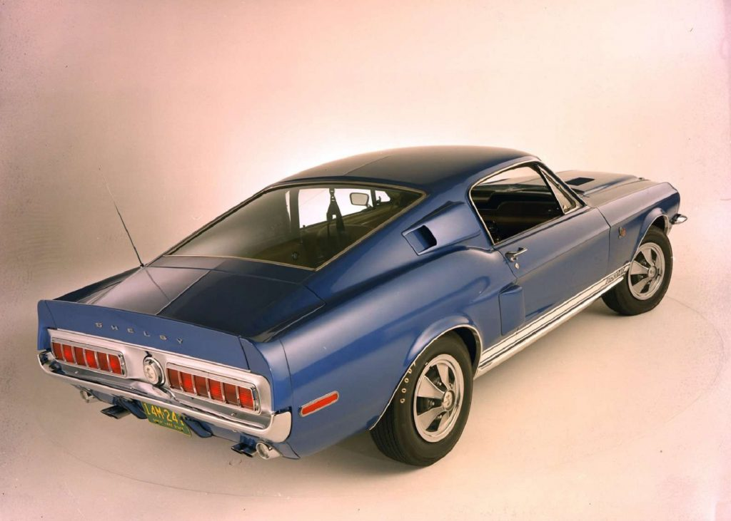 The rear 3/4 view of a blue-and-white 1968 Shelby GT500KR Mustang