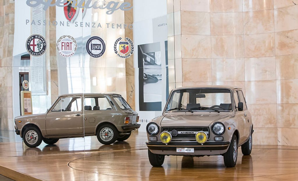 A brown 58-hp 1971 Autobianchi A112 Abarth in front on a mirrored Stellantis stand