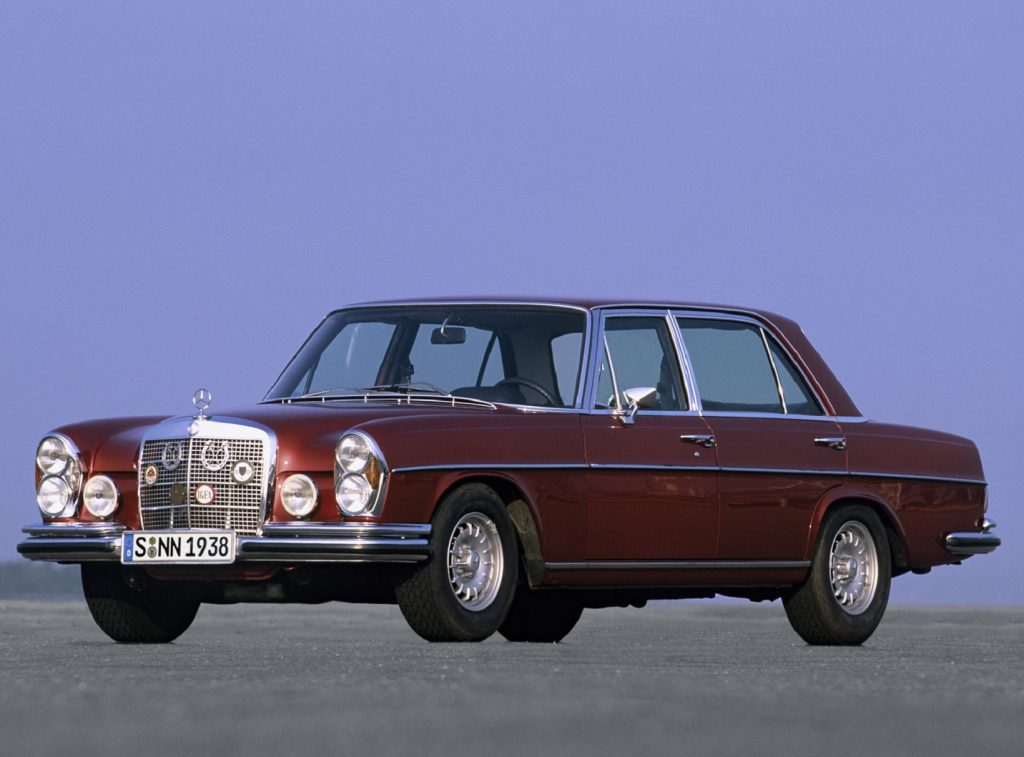 A maroon 1971 Mercedes 300 SEL 6.3 on a runway