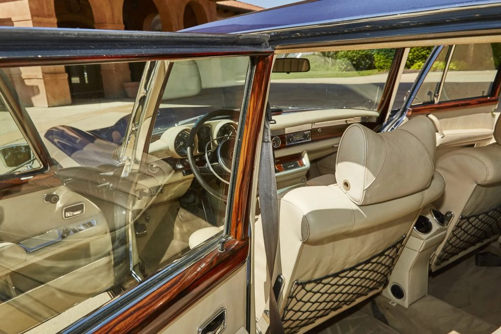 The white-leather and brown-wood-trimmed interior of a blue 1971 Mercedes 600