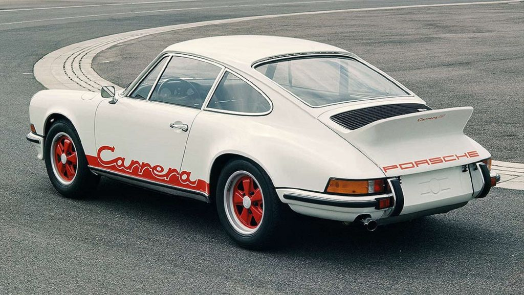 The rear 3/4 view of a white-with-red-graphics 1973 Porsche 911 Carrera 2.7 RS on a racetrack