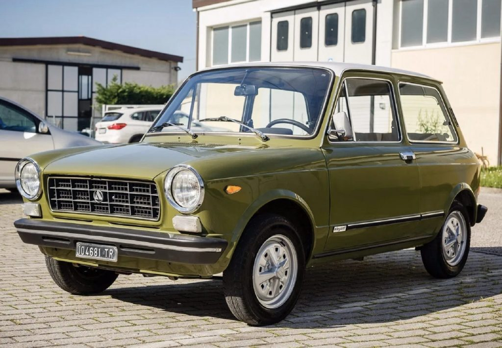 A green 1974 Autobianchi A112 parked in a crowded parking lot