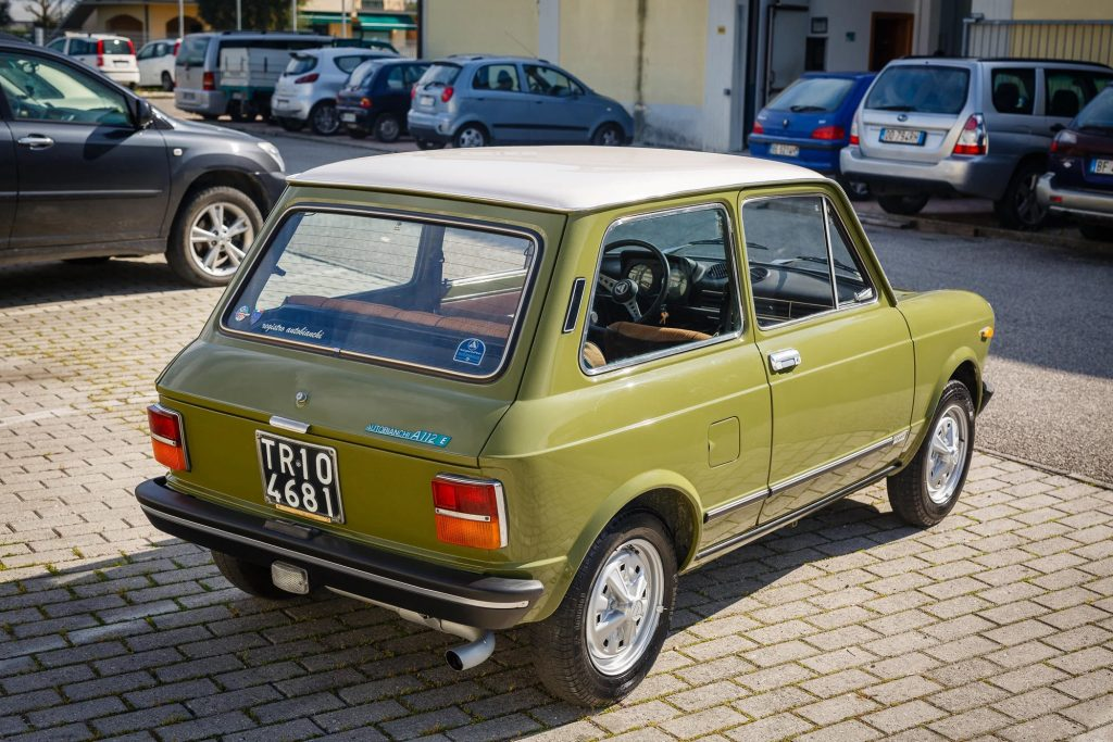 The rear 3/4 view of a green 1971 Autobianchi A112 Abarth in a crowded parking lot
