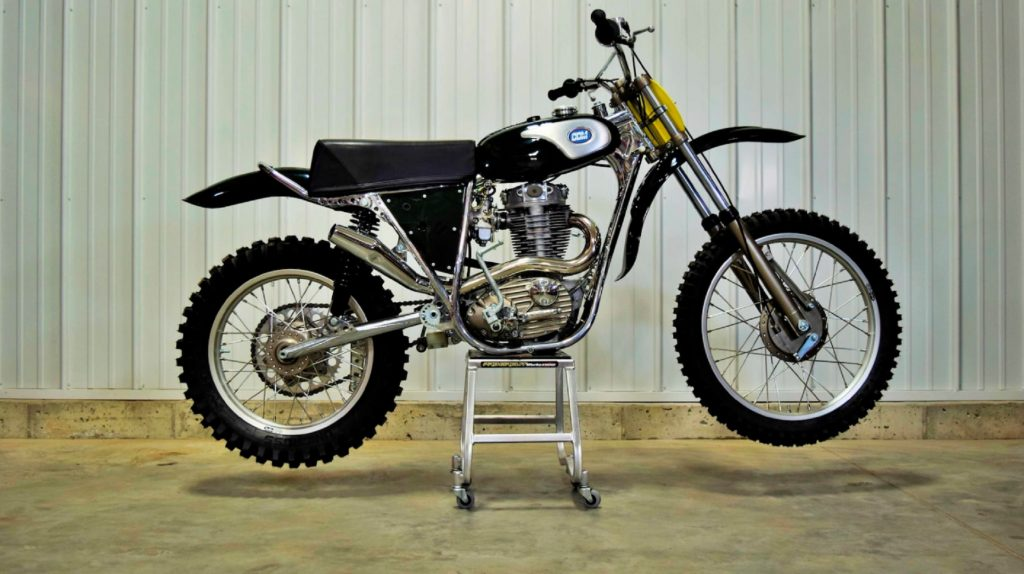 A black-and-chrome 1974 CCM 605 John Banks Replica motocross motorcycle on its stand in a warehouse