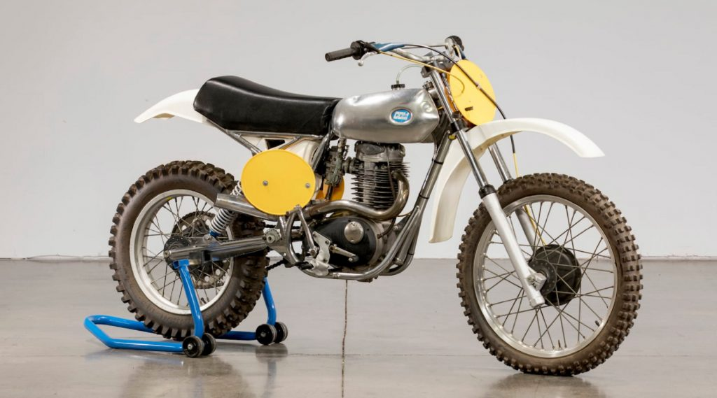 A yellow-white-and-chrome 1976 CCM Cross 4-Stroke motorcycle on a blue rear-wheel stand