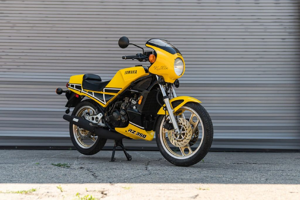 A yellow-and-black 1984 Yamaha RZ350 Kenny Roberts Edition by a garage door