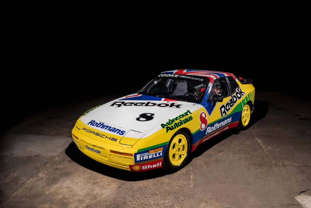 A multi-colored Rothmans-liveried 1988 Porsche 911 Turbo Cup in a warehouse