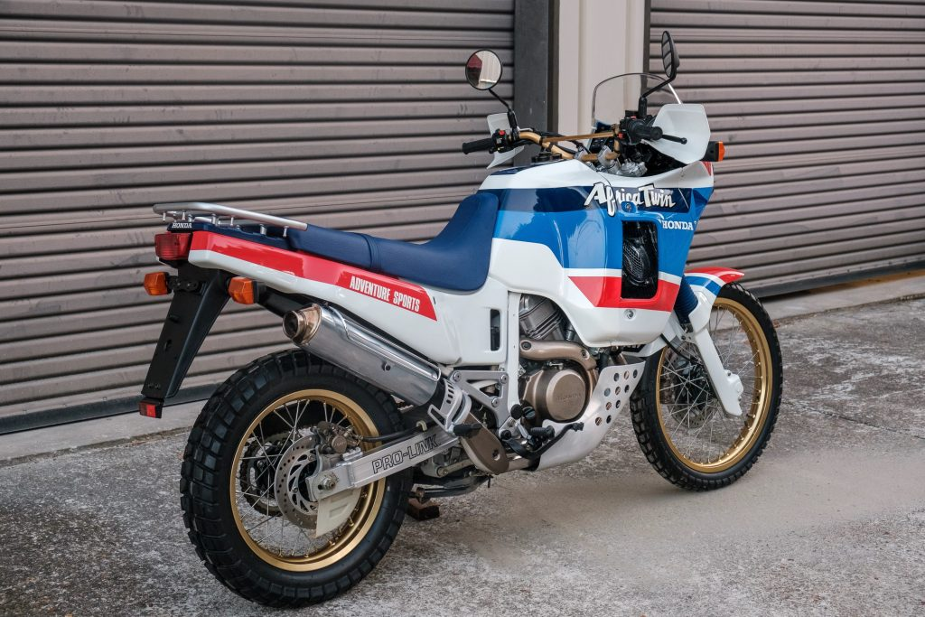 The rear 3/4 view of a white-blue-and-red 1989 Honda Africa Twin XRV650 by a garage