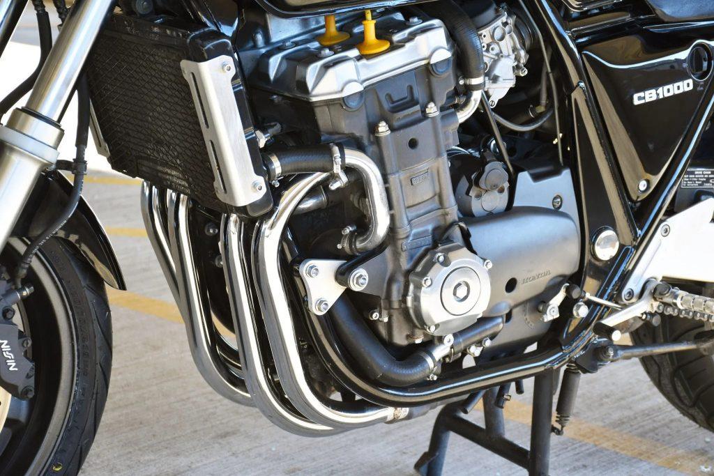 A close view of a black 1994 Honda CB1000 Super Four's liquid-cooled 998cc inline-four engine