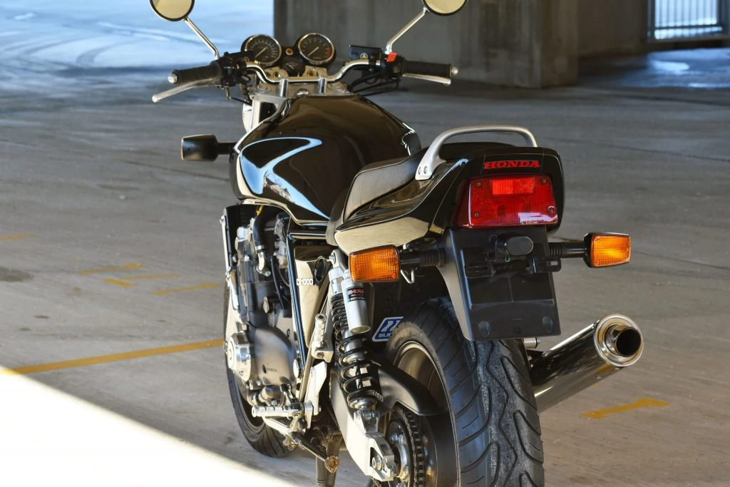 The rear 3/4 view of a black 1994 Honda CB1000 Super Four in a sunny parking garage