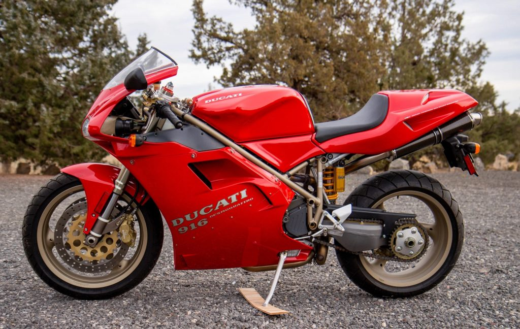 The side view of a red 1997 Ducati 916 parked on a gravel area by a forest