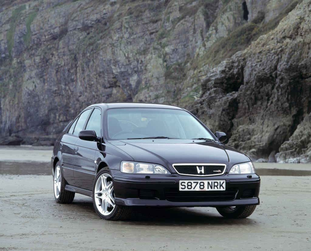 A black 1999 Honda Accord parked in front of beach side cliffs