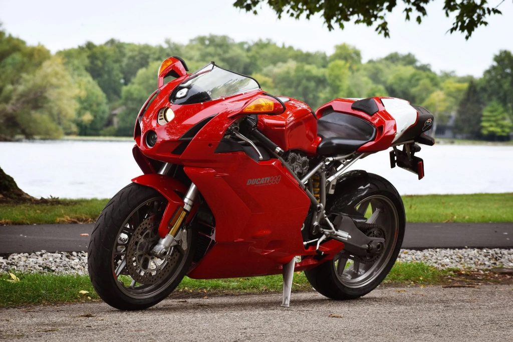 A red 2003 Ducati 999 by a forest lake