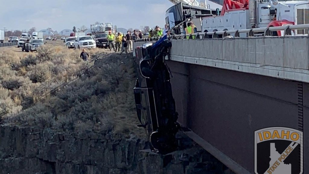 A 2004 Ford F-350 suspended over the edge of a bridge by tow chains