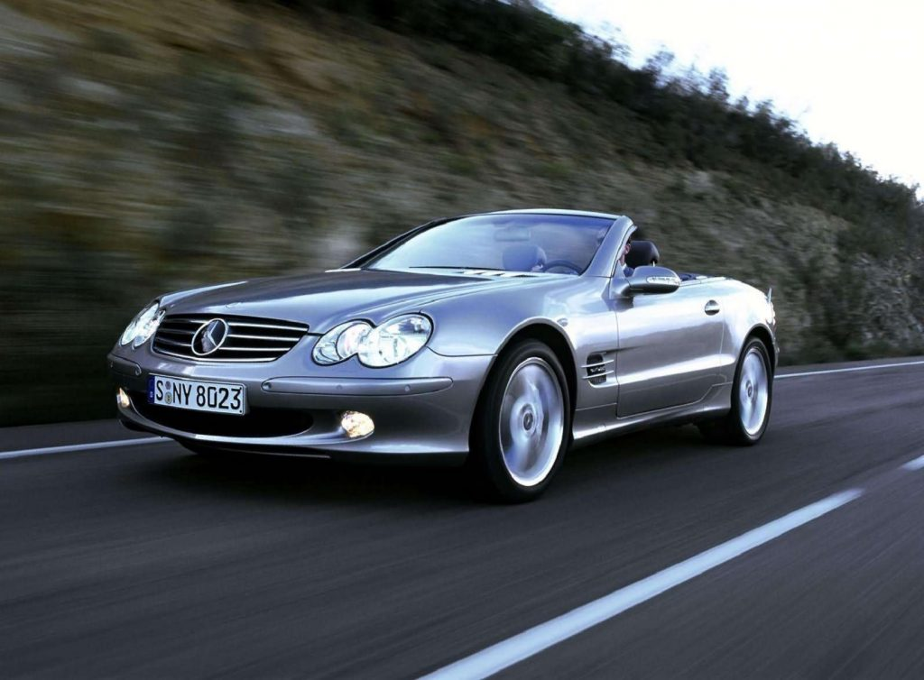 A silver 2004 Mercedes-Benz SL600 with its roof down driving down the road by a rocky cliff