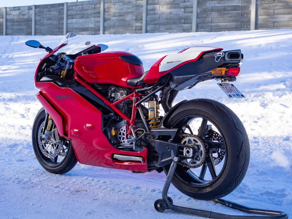 The rear 3/4 view of a red-and-white 2005 Ducati 999R on a rear-wheel stand parked on snow