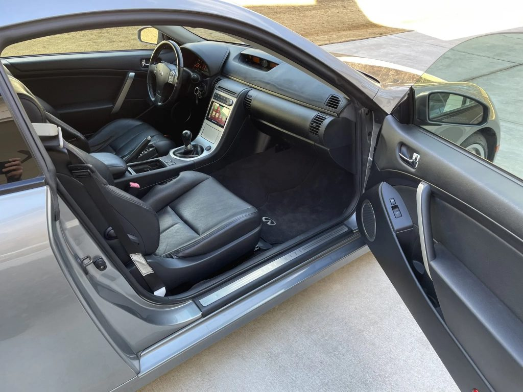 The black-leather front seats and aluminum-trimmed center console of a modified 2005 Infiniti G35 Coupe seen from the open door