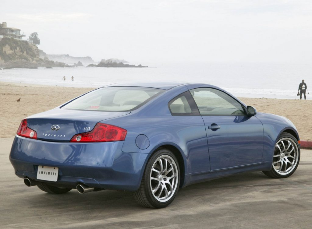 The rear 3/4 view of a blue 2005 Infiniti G35 Coupe parked by the beach