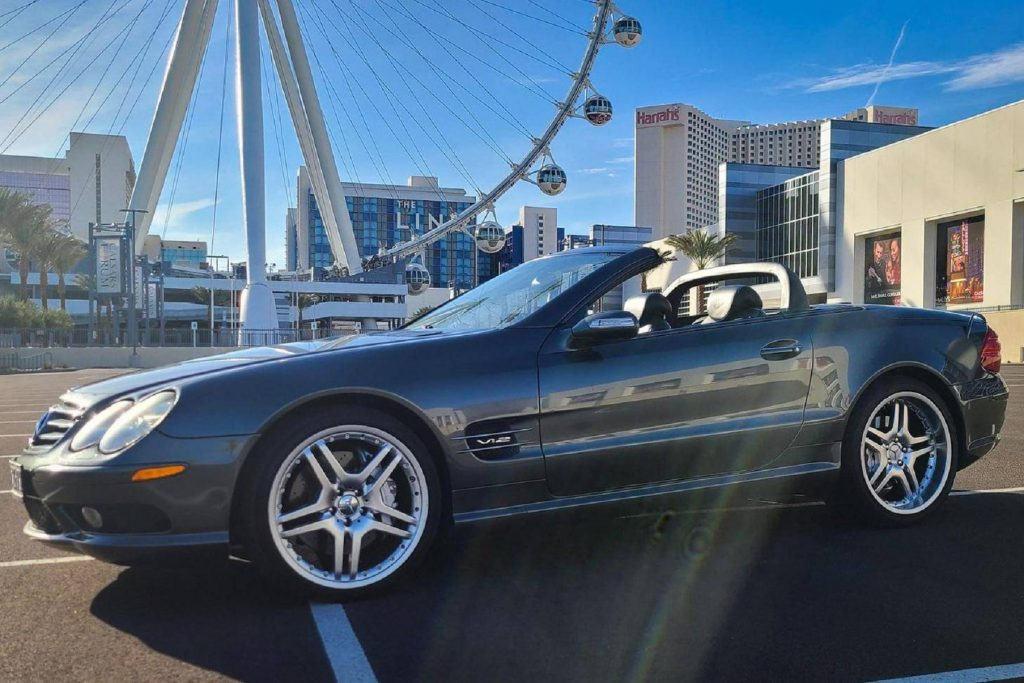 The side 3/4 view of a dark-gray 2005 Mercedes-Benz SL600 with its roof down by a Ferris wheel in a city parking lot