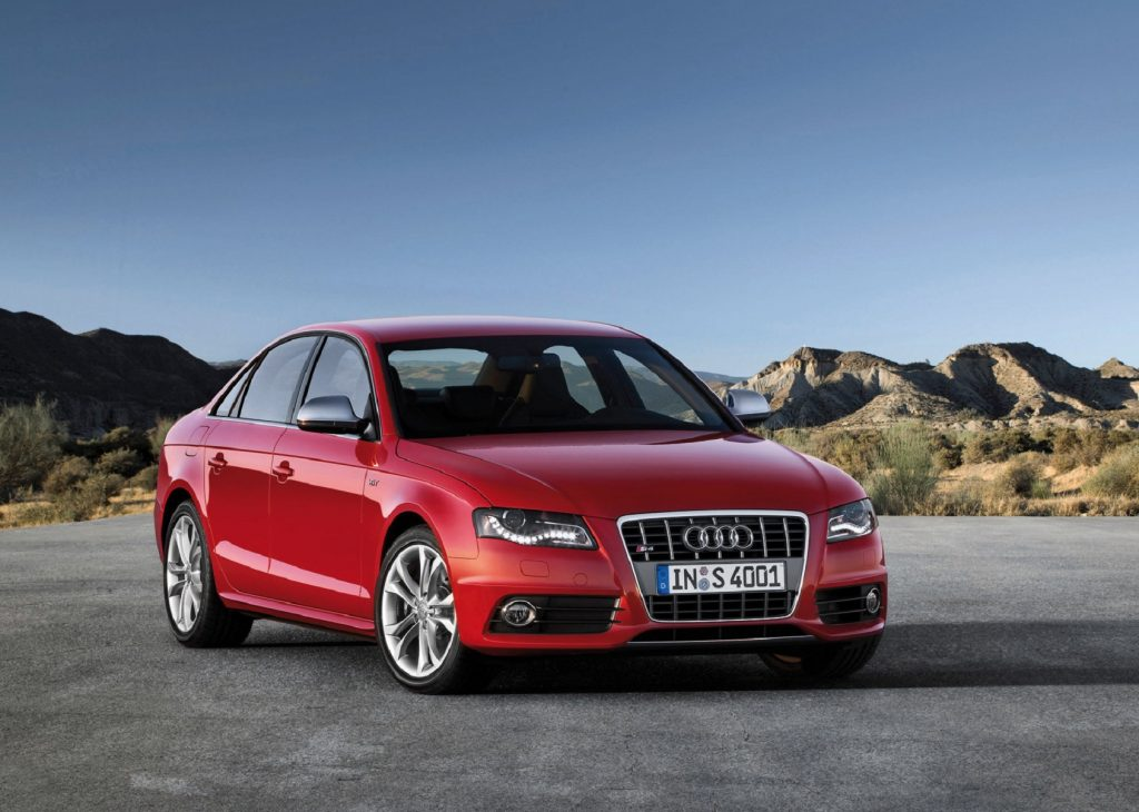 A red 2010 B8 Audi S4 parked on a mountainside parking lot