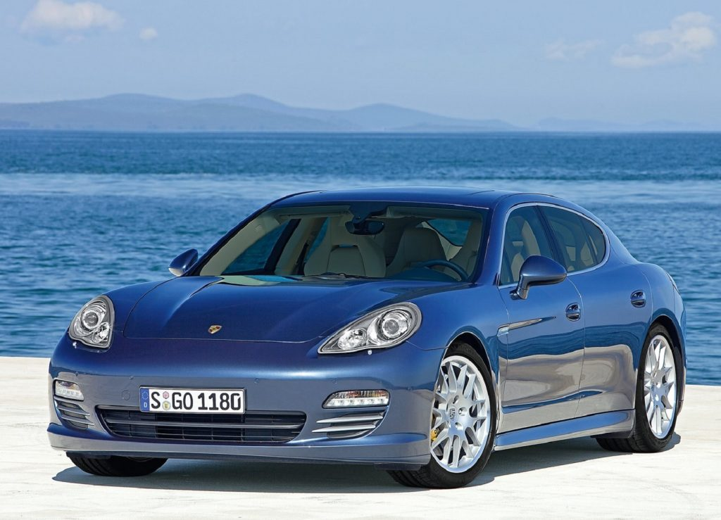 A blue 2010 Porsche Panamera 4S parked on a pier by the ocean