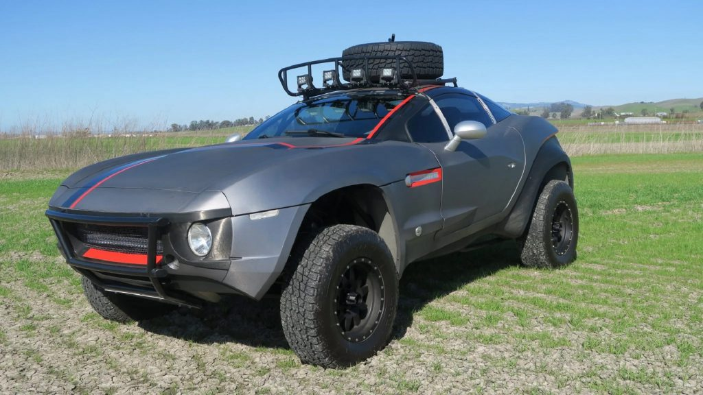 A gray-and-red 2011 Local Motors Rally Fighter with a roof-mounted basket in a field