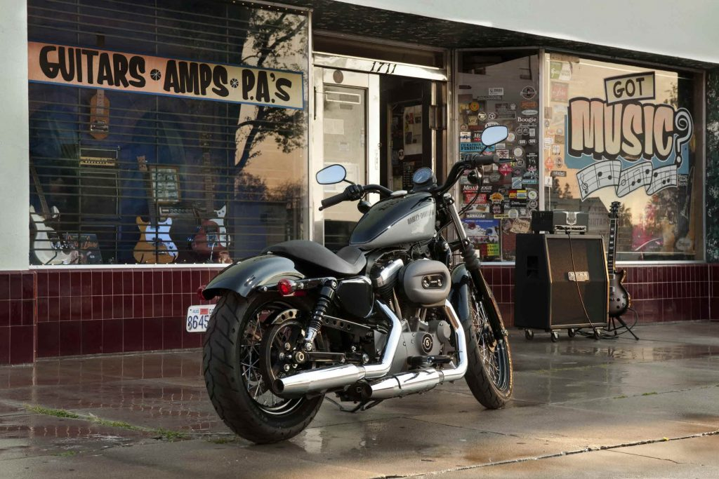 The rear 3/4 view of a gray-and-black 2012 Harley-Davidson Nightster parked by a record store