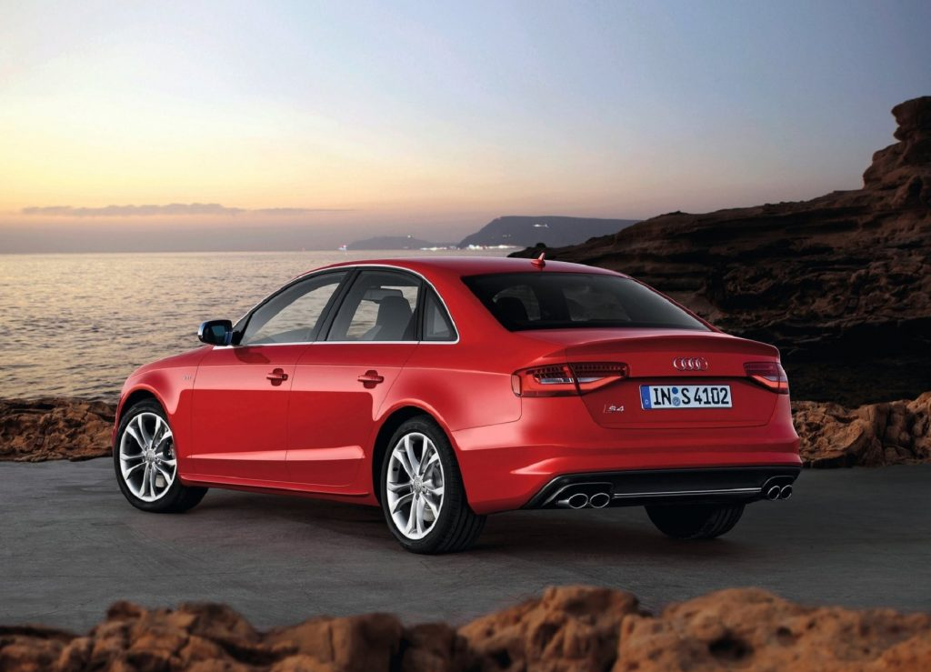 The rear 3/4 view of a red 2013 Audi S4 parked by some oceanside cliffs