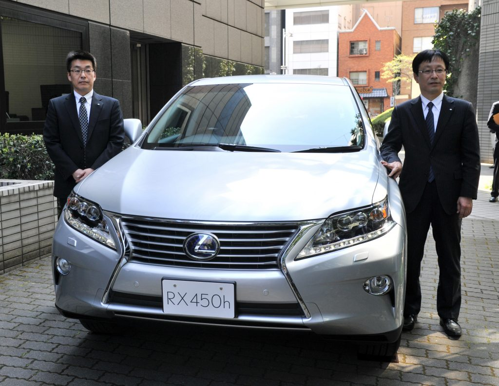 Japan's auto giant Toyota Motor managing officer Kazuo Ohara (R) introduces the company's newly designed Lexus RX 450h hybrid SUV with a 3.5-litre V6 engine
