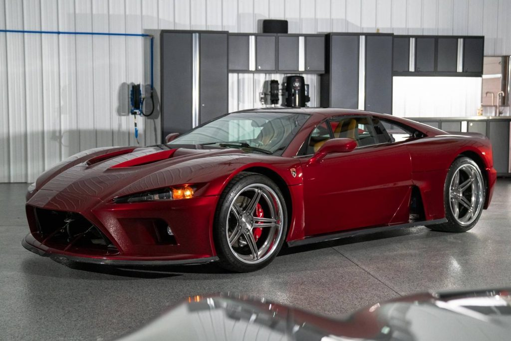 A maroon 2014 Falcon F7 parked in a car garage in front of a silver car