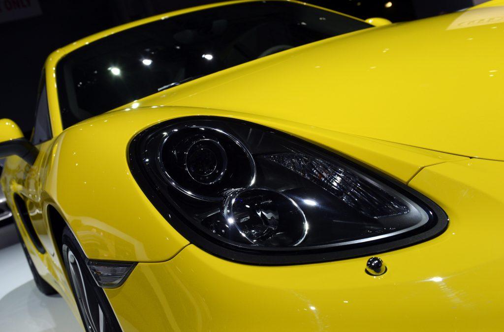 A yellow Porsche Cayman coupe
