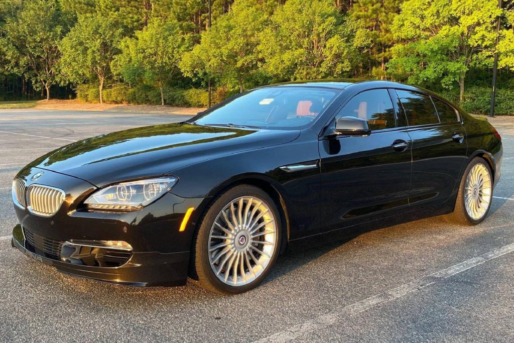 A black 2015 BMW Alpina B6 xDrive Gran Coupe parked on a sunset-lit tree-lined parking lot