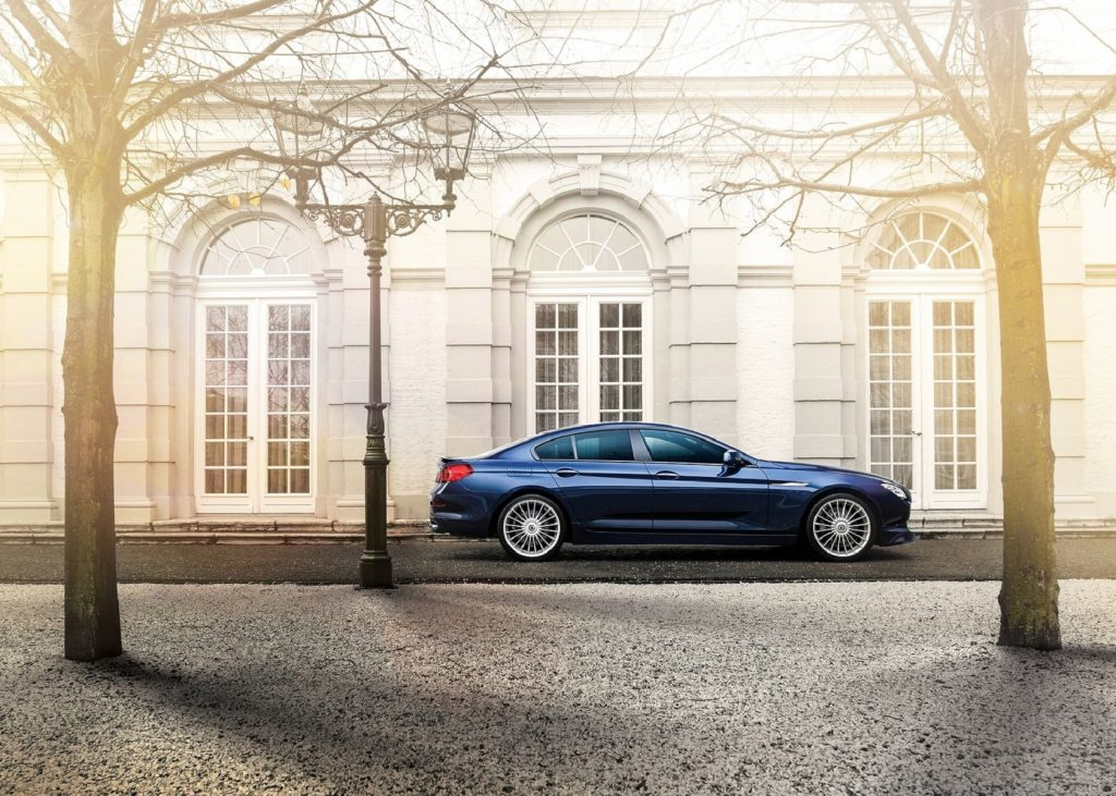 The side view of a dark-blue 2015 BMW Alpina B6 xDrive Gran Coupe by a white old building