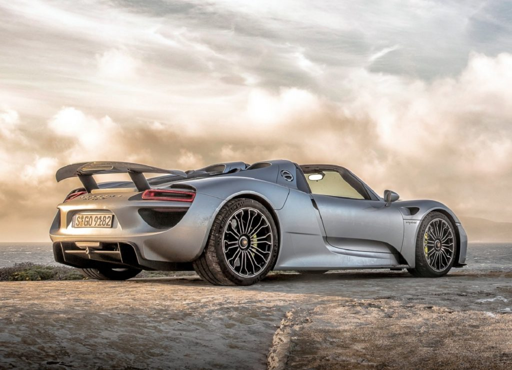 A low-angle rear 3/4 view of a silver 2015 Porsche 918 Spyder on a sandy beach