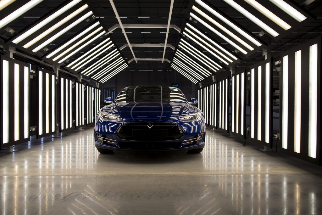 A blue 2015 Tesla Model S electric sedan under rows of lights