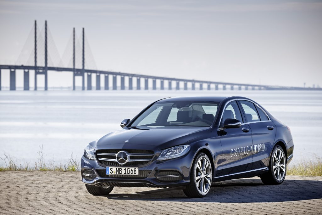 A blue 2016 Mercedes-Benz C-Class (C350e) parked next to the water with a bridge in the background