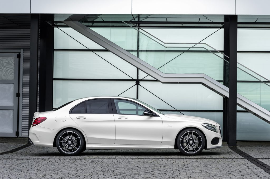 A white 2016 Mercedes-Benz C450 AMG 4MATIC parked next to an artsy wall