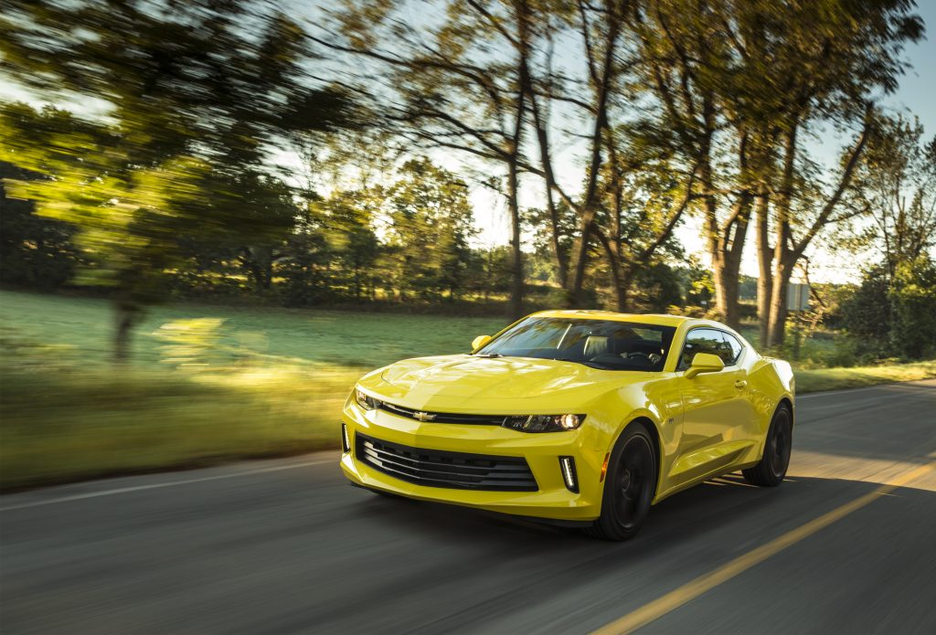 A yellow 2017 Chevy Camaro driving down a country road with trees in the background