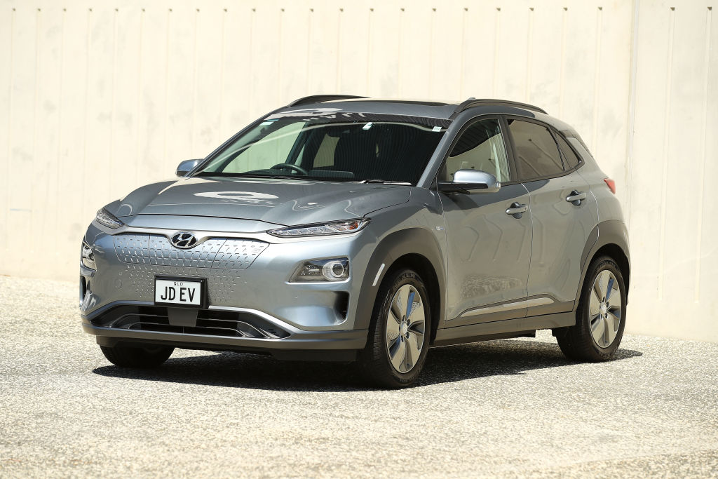 A silver Hyundai Kona EV parked in front of a beige concrete building
