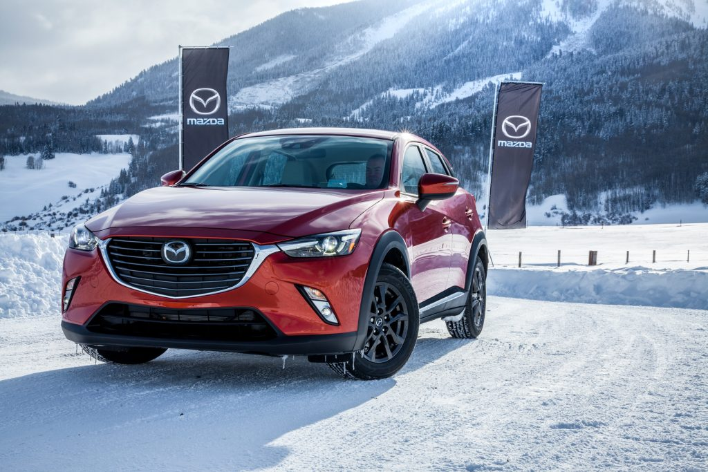 A red 2017 Mazda CX-3 parked in the show with Mazda flags in the background