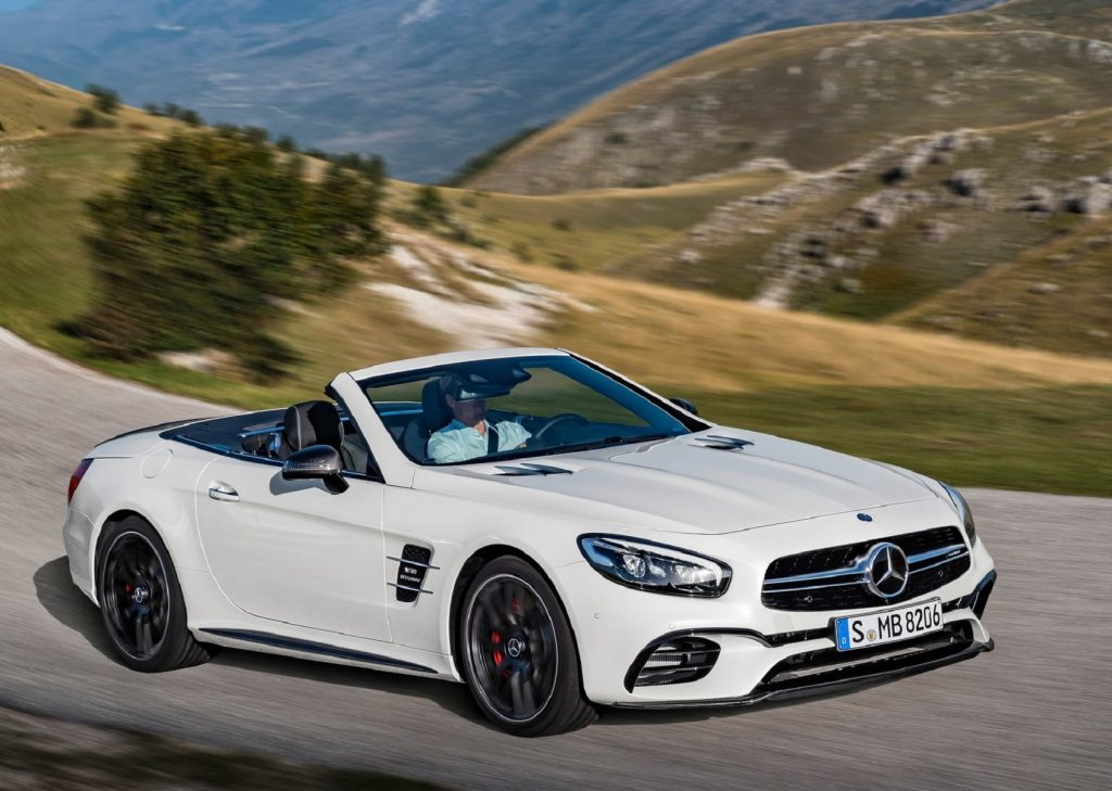 A white 2017 Mercedes-Benz SL 63 AMG driving through the mountains with its roof down