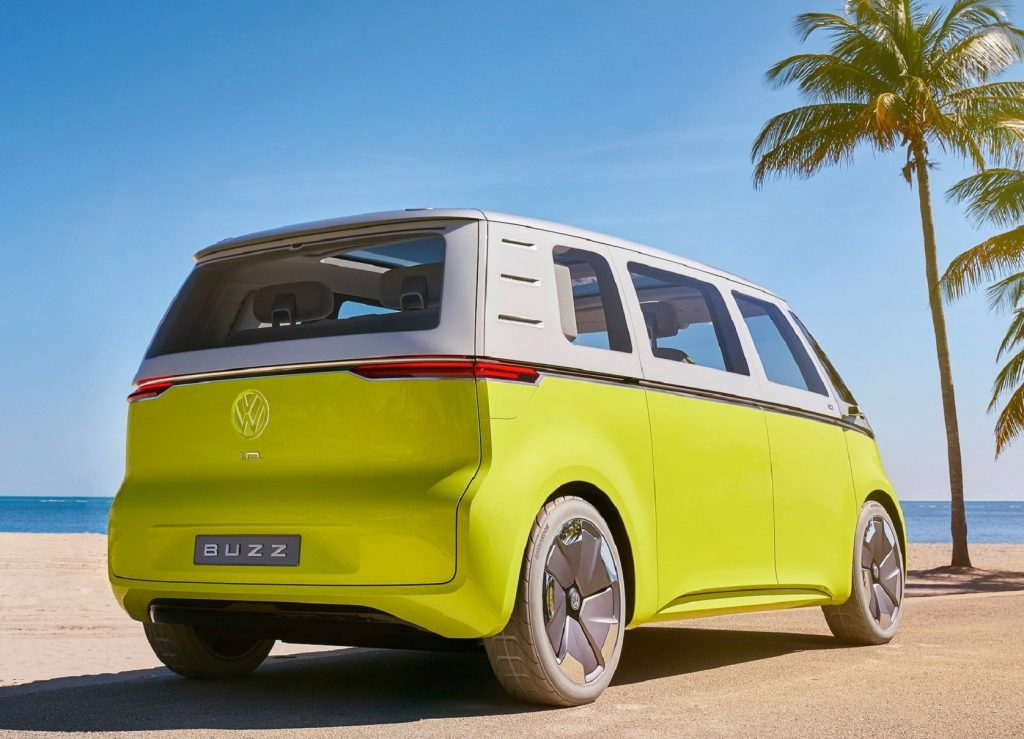 The rear 3/4 view of a yellow-and-silver 2017 Volkswagen ID.Buzz Concept parked on a sandy beach