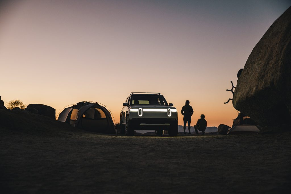 The Rivian electric SUV, the R1S parked in the desert at dusk