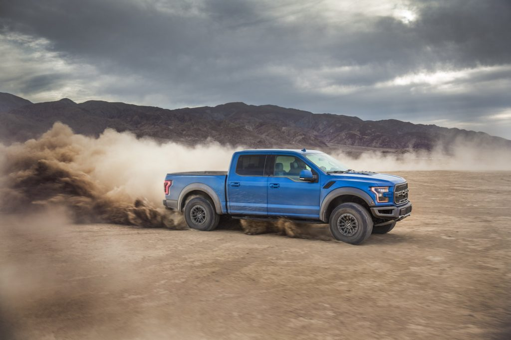 A blue 2019 Ford F-150 Raptor four-door pickup truck kicks up dust as it drives on dirt in front of a mountain on a cloudy day