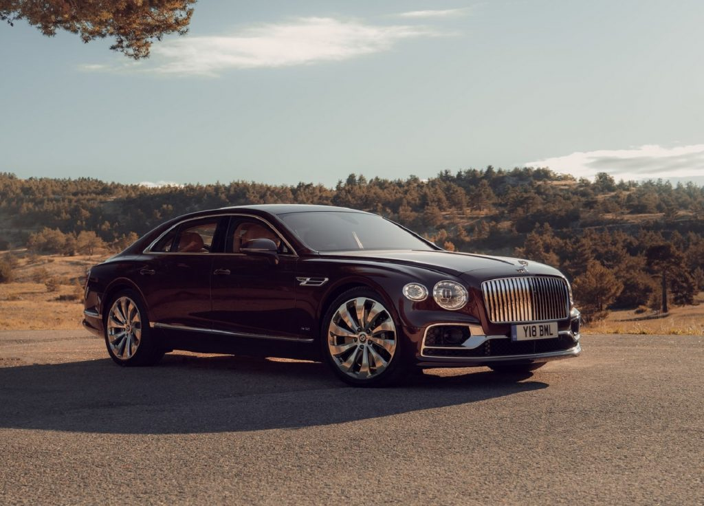 A maroon 2020 Bentley Flying Spur parked by sunlit tree-covered hills