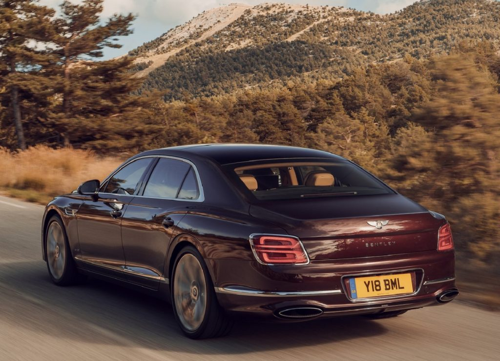 The rear 3/4 view of a maroon 2020 Bentley Flying Spur driving on a tree-lined mountain road at sunset