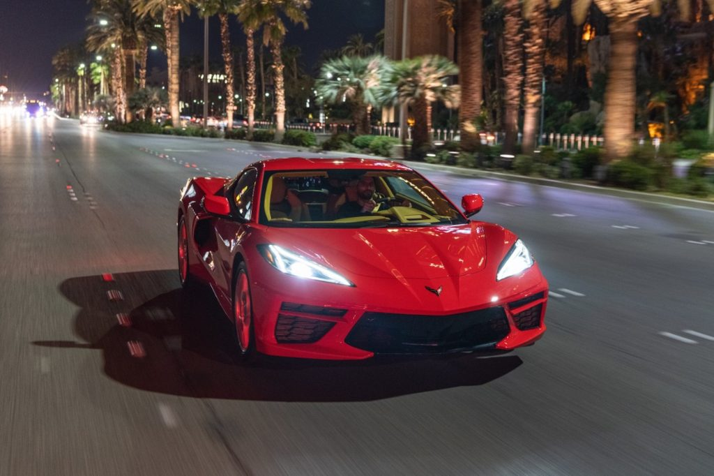 A red 2020 Chevy Corvette Stingray sports car travels at night on a multilane highway with palm trees in the median