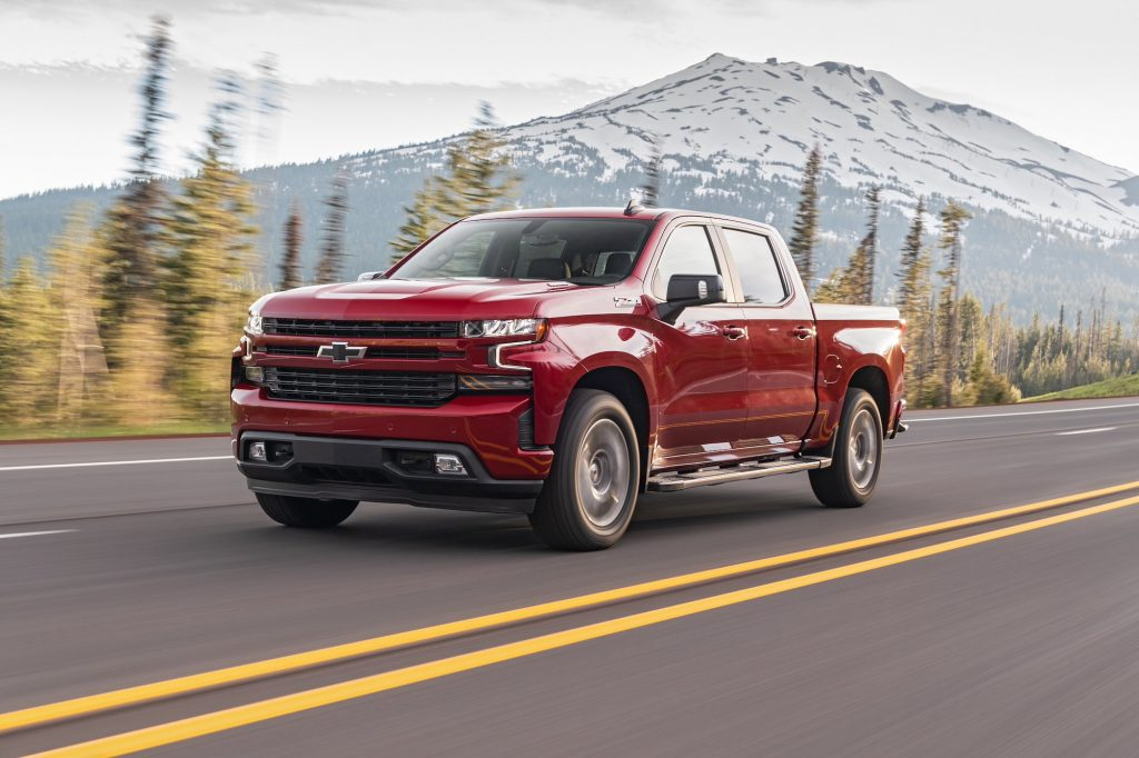 A red 2020 Chevrolet Silverado Diesel full-size pickup truck travels on a four-lane highway past pine trees and a snow-capped mountain
