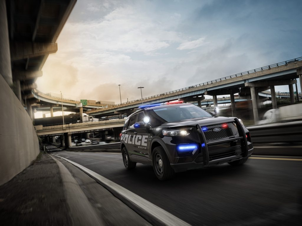 A black 2020 Police Interceptor Utility vehicle with its lights on travels on a highway entrance ramp